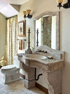 Whether ancient or reproduction, architectural relics go a long way in establishing Mediterranean style. From the rustic tiles underfoot to the carved stone vanity and stone-framed mirror, this bathroom emphasizes old-world forms and textures. Stone Bathroom, Small Bathroom, Glass Bathroom, Bathroom Lighting, Bathroom Ideas, Mediterranean Baths, Mediterranean Style, Old London, Traditional Bathroom