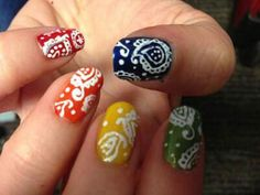 Nails with red, orange, yellow, green, and blue bases and intricate white designs on top