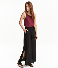 Black. Long skirt in crinkled, woven viscose fabric. Elastication and drawstring at waist with tassels. Slits at sides. Unlined.