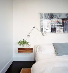 Floating bedside table. Minimizes clutter, while providing space for necessary evils like alarm clocks.