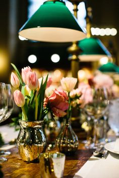 Emerald green lamps above a golden table