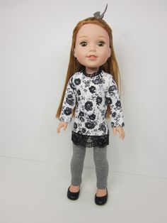 Gray and black flowered tunic top with gray leggings outfit by JazzyDollDuds on Etsy. Made following a modified version of the T-Shirt Variations for and the UK Holiday Top and Leggings for WellieWishers Dolls patterns. Get them at http://www.pixiefaire.com/products/t-shirt-variations-for-welliewishers-dolls. http://www.pixiefaire.com/collections/doll-clothes-patterns-for-wellie-wishers-and-hearts-for-hearts-girls/products/u-k-holiday-top-and-leggings-for-welliewishers-dolls. #pixiefaire…