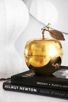 Buy a plastic fruit and spray it into gold. This one is a candle, but looks lovely. Gold Apple Candle | Trendenser
