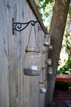 DIY: Backyard lighting. Mason jar with Sand, Pebbles, or even Salt rocks and a tealight or votive on a wall hook drilled in to the fence.