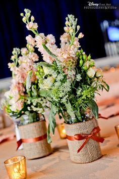 Mason jar centerpieces dressed up with burlap, ribbon and floral