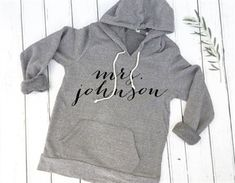 Custom mrs hoodie. Any text possible! If personalization includes last name, please include the last name and color of hoodie preferred in the notes to seller section at checkout. If other text is…More #brideshirt #personalizedshirt #custombrideshirt #etsyparty #bridegifts #bridal #personalisedtshirt #tanktops #customgifts #bridesmaid #bridalshowertshirts #bridesmaidgifts #bridesmaidshirts #bridesmaidtshirt #shirts #tshirts #etsy #bridalshirts #bride #etsyclothes Wedding Day Shirts, Bridal Shirts, Brides Maid Shirts, Bride Sweatshirt, Brides Maid Proposal, Bridal Outfits, Brie, Bridal Shower, Sweatshirts