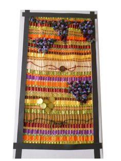 Colourful woven textile on a frame with purple surface texture reminiscent of bunches of grapes and what appear to be representations of gold coins.