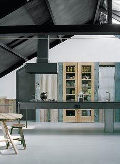 cocina rústica con pavimento continuo e isla central con fregadero y zona de cocción, para la zona de almacenaje se utilizan muebles de madera reciclada y vitrina