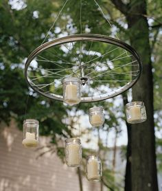 14 Ways to Repurpose a Bicycle Wheel.  Hang glass jars with candles inside from a bike wheel.  Then hang the whole thing from a tree-branch.