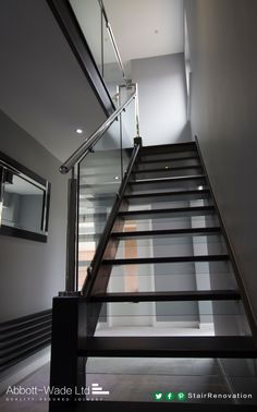 An open tread black oak staircase with steel rail & glass balustrade. Glass risers add to the feeling of openness while ensuring this new flight meets current building regulations