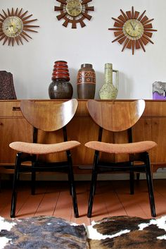 G Plan Chairs, sideboard, fat lava esque ceramics and starburst clocks.  Mid-Century staples