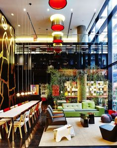 Lit byTom Dixon pendant lights, a long tableis a natural gathering placefor travellers inthe lobby of New York's zany CitizenM.    This originally appeared in Bright Hotel with Spacious Communal Lobby in Times Square.