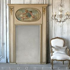 Eloquence, Inc.Antique French Trumeau with Angel Painting: 1910 Lovely Antique Trumeau Mirror in dusty beige with parcel gilt finish with gilt appliques. The top features a darling cherub inset painting in delicate pastels. This mirror exhibits a delicate side of classic French style.