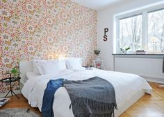 Relaxing bedroom with floral wallpaper and warm wooden flooring