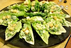 You Will Need  Endive or romaine lettuce leaves Caesar salad dressing Mini croutons (prepared, or homemade!) Parmesan cheese  Direction