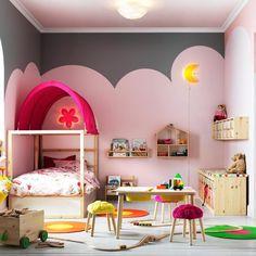 Une chambre d'enfant aux murs poétiques. Cette chambre d'enfant s'habille d'un nuage rose tracé sur ses murs. Petit plus de cette pièce : le coin lecture pour accompagner ce voyage au pays des rêves.