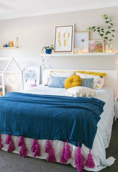 Picture ledge above the headboard, lights draping down... // A colorful bedroom
