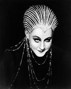 Brigitte Helm's Yoshiwara Costume From Metropolis For the first feature-length sci-fi film in history, Fritz Lang did well to cast Brigitte Helm in the adaptation of his wife Thea Von Harbou's novel turned silent movie, Metropolis. But even better to outfit her in a glorious, sparkling, alien cap that looks like water beads on a flower. The hat makes her widow's peak its central focus and the hair pouf its afterthought. It's very sinister, and Art Deco.