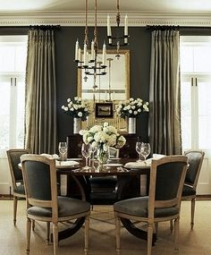A traditional dining room becomes edgy and elegant when deep, sultry grey is mixed with creamy neutrals.  Glistening glassware and an over sized mirror naturally reflect light throughout the space.