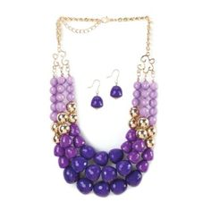 """by Breezy Couture Three rows of dazzling orchid tonal faceted beads will make a stunning statement about your style! This pretty necklace also features golden beads that shimmer in the light, and the matching purple dangle earrings are the perfect complement.  Necklace: 18"""" long, extended to 21"""" long; each earring is 1"""" long. California Prop 65"""