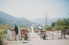 super cool small ceremony mismatched dinner chairs, flowers, chalkboard, plants, flowy altar backdrop