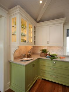 This light and airy kitchen is livened up by a bright pop of color, in this case a bright green on the base cabinets. Glass-front cabinets and a paneled and beamed ceiling serve to add extra character.