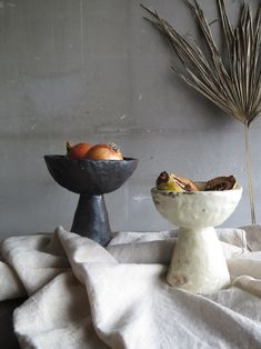 Pedestals, both of mixed clay bodies in matte black and white.