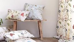 James Hare -  Orchard Silk Fabric Collection - A small light wood bench with floral patterned scatter cushions and curtains in cream, pale blue,red, green and white