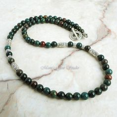 This handsome mens necklace was made with natural Bloodstone well-polished beads in deep forest green, moss green, some maroon, brown and gray with occasional red spots that resemble blood, which said to be the blood of Christ in legend. I added antiqued silver finish pewter beads to accentuate the necklace, and finished off with a pewter toggle clasp. All metal materials are lead-safe. The pictures represent a similar item you will receive in quality and shades.  Length Option: Length…