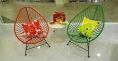 These red and green Acapulco chairs have a very retro look that is highlighted with decorative pillows.