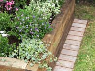 Raised beds are a great way to separate your garden from your lawn. To make mowing around them easier, follow these steps from HGTV Gardens to build an edge using spare brick.