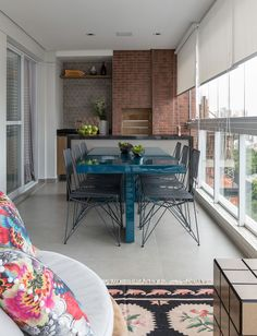 Decoração de apartamento, apartamento, apartamento moderno, apartamento cinza, cinza.  Na varanda parede de tijolinhos, plantas, mesa de jantar retangular azul.