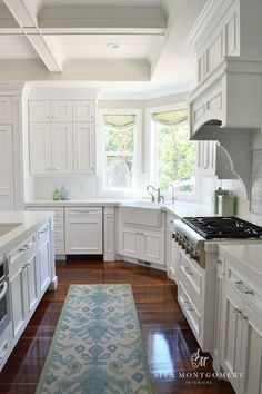 All white kitchen with warm hardwood floors. White Coffer ceiling and multiple windows in this custom white kitchen.