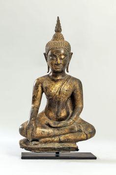 Buddha Maravijaya assis en bumishparshamudra dans la prise de la terre à témoin, vêtu de la robe monastique utarsanga, le visage serein surmonté d'un haut rasmi flammé. Bronze doré à patine de fouille. Thaïlande. Royaume d'Ayutthaya. 17 ème siècle. Ht 34cm x larg 20 cm. Cassure à la base.