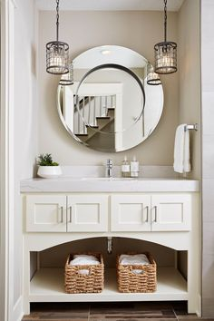 Pairing traditional and contemporary style together, this vanity mixed a sleek round mirror with hanging pendants and a beautiful cream vanity for an all-around fresh and updated look.