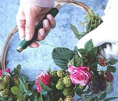 Beginnen Sie nun an einer Seite des Weidenrohlings mit dem Binden und Drapieren. Rosen und Brombeerzweige können Sie jeweils gut zu einzelnen kleinen...