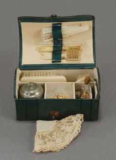 Fashion Doll Necessaire - Housed inside is an assortment of toilette articles that includes ox bone handled brushes – including a toothbrush, hairbrush etc., a silver metal lidded receptacle complete with face powder inside, a swans down puff, a mirror, an assortment of glass bottles for toilet water, a crochet hook, a fan and a hankie. Carmel Doll Shop - SOLD $2,250