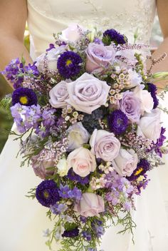 Purple, lilac and pale pink roses, aster, lysianthus...not sure what the purple flowers with yellow centres are...