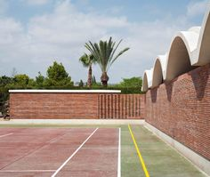 Mesura adds red brick extension with scalloped roofline to Alicante residence.