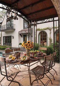 terrace style open air room under an iron trellis canopy
