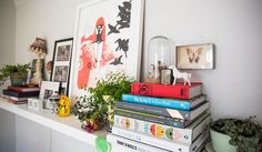 A long white shelf holds two stacks of books, three leafy house plants and an array of small ornaments including a tiny white horse and a golden Chinese lucky waving cat.