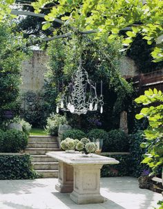 A Tyson Bennison chandelier hanging from a Wisteria draped pergola poised artfully over the stone table in his Regency house courtyard in Battersea (South London).