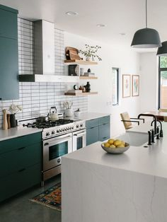Muuto Pendants. Cambria Waterfall Island. Leather West Elm Barstools and White Triangle Tile Backsplash. White Glazed Brick 2x8 Subway Tile from Fireclay with Painted Green Kitchen Cabinets and Floating White Oak Shelves. Matte Black Hardware and Stainless Steel Range, Hood, and Appliances. Our Austin Casa || The Kitchen Reveal - The Effortless Chic