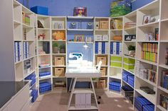 """""""I told my designer I wanted a table for my sewing machine and storage to do arts and crafts with the kids and I was blown away by what she came up with,"""" Kathy Graivier  says. The shelves and art were purchased from Ikea and the concrete walls were painted blue to make the windowless room appear more inviting."""