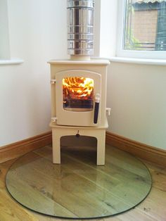 NB: Walls behind treated with sand and cement render and heat proof skim! The 'Cove on log store in almond is a Wood burning stove placed on a teardrop shaped, clear glass hearth. (Found @ Fahren Corner Fireplace, Home, Fireplace Gallery, House, Hearth, Stove, Wood, Wood Burning Stove, New Homes