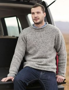 GREY ROLL NECK SWEATER WITH ORANGE UNDERSHIRT. SUBTLE NOD  TO SPACE SUITS.