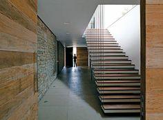 Para minimizar as barreiras visuais, a escada é vazada de um lado e, do outr...