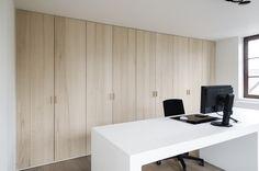 Rustige kantoorruimte, door slanke belijning van het bureau, rustig kleurgebruik en de warme uitstraling van het hout van de kasten.
