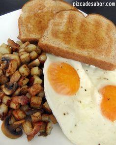 Ricas papas doraditas y crujientes con tocino y champiñones para acompañar unos huevos estrellados. Un desayuno de campeones. ¡Te deja bastante satisfecho toda la mañana!
