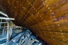 Nail holes filled with putty and freshly oiled timber hull planks on a dhow under construction. Sur, Ash Sharqiyah Region, Gulf of Oman, Sultanate of Oman.